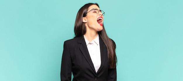Giovane bella donna che urla furiosamente, grida in modo aggressivo, sembra stressata e arrabbiata. concetto di business