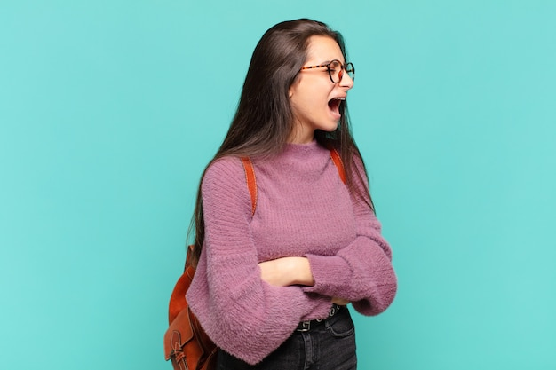 Giovane donna graziosa che grida furiosamente, grida in modo aggressivo, sembra stressata e arrabbiata