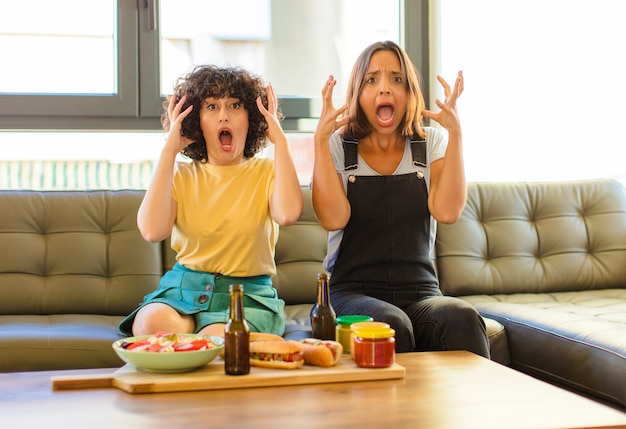 Giovane donna graziosa che grida con le mani in alto, sentendosi furiosa, frustrata, stressata e sconvolta