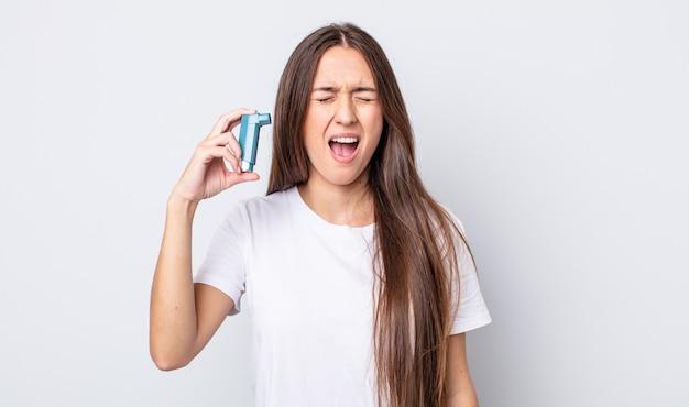 Giovane bella donna che grida in modo aggressivo, sembra molto arrabbiata. concetto di asma
