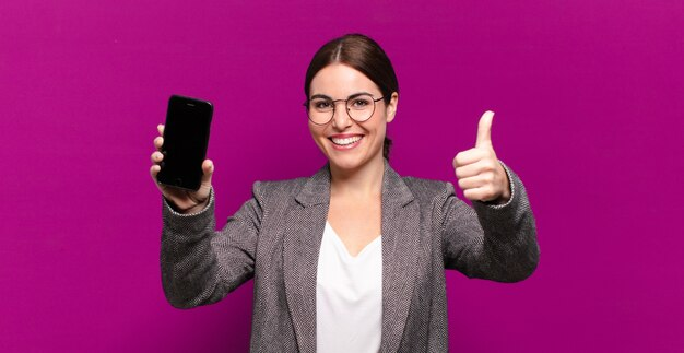 Giovane donna graziosa che mostra il suo telefono a schermo vuoto. concetto di business