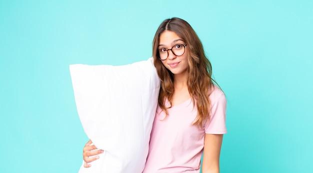Giovane bella donna che scrolla le spalle, si sente confusa e incerta indossando un pigiama e tenendo in mano un cuscino