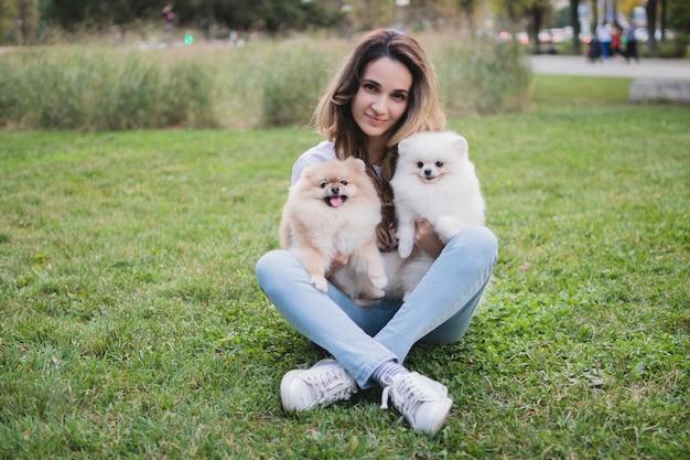 Una giovane donna graziosa si siede sull'erba verde e tiene in braccio i suoi amati cani di pomerania.