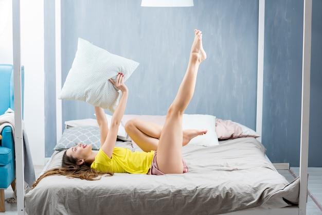 Giovane bella donna in pigiameria che gioca con il cuscino in camera da letto