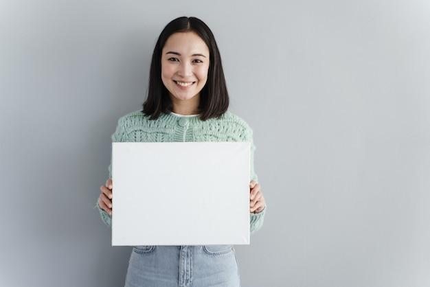 La giovane donna graziosa sorride e tiene il pezzo di carta in bianco nelle sue mani