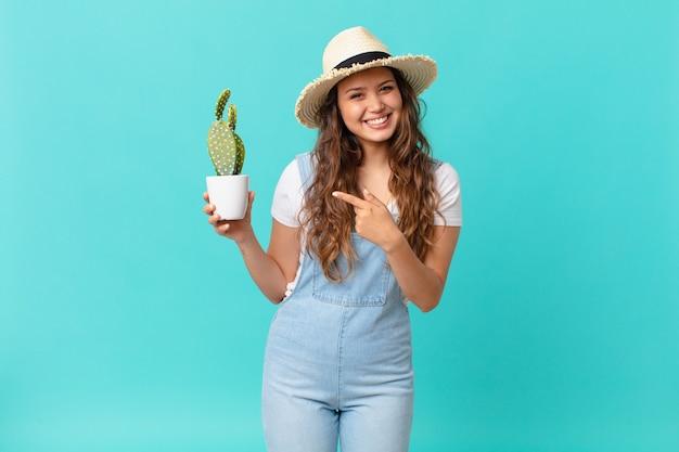 Giovane bella donna che sorride allegramente, si sente felice e indica il lato e tiene in mano un cactus