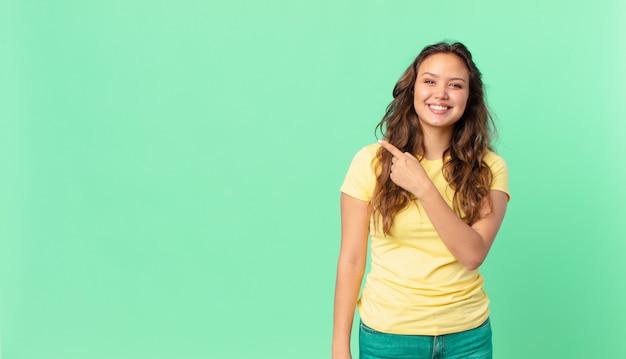 Giovane bella donna che sorride allegramente, si sente felice e indica il lato e indica lo spazio della copia
