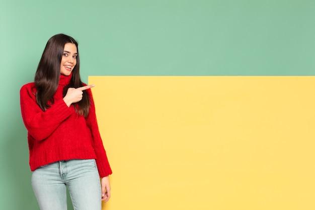 Giovane bella donna che sorride allegramente, si sente felice e indica il lato e verso l'alto, mostrando l'oggetto nello spazio della copia. copia spazio per posizionare il tuo concetto