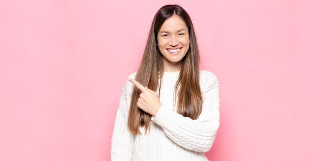 Giovane donna graziosa che sorride allegramente, sentendosi felice e indicando il lato e verso l'alto, mostrando l'oggetto nello spazio della copia
