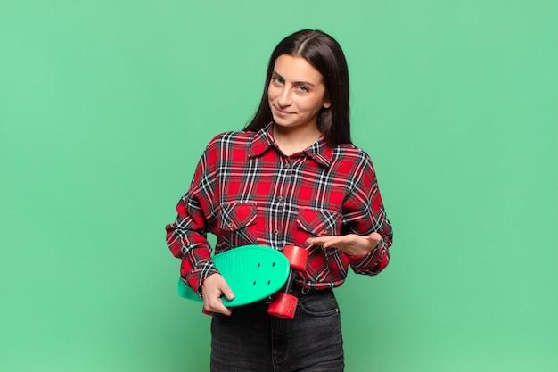 Giovane bella donna che sorride allegramente, si sente felice e mostra un concetto nello spazio della copia con il palmo della mano. concetto di skateboard
