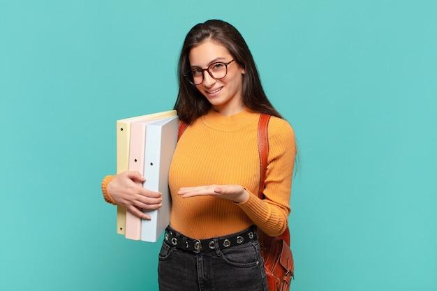 Giovane donna graziosa che sorride allegramente, sentendosi felice e mostrando un concetto nello spazio della copia con il palmo della mano. concetto di studente