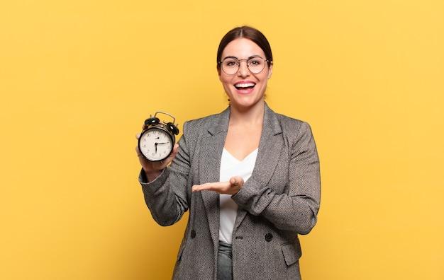 Giovane donna graziosa che sorride allegramente, sentendosi felice e mostrando un concetto nello spazio della copia con il palmo della mano