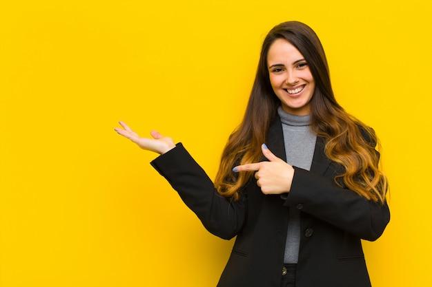 Giovane donna graziosa che sorride allegramente e che indica lo spazio della copia sulla palma dal lato, mostrando o pubblicizzando un lavoro dell'oggetto o un concetto di affari