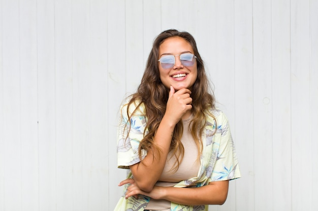 Giovane bella donna sorridente, godersi la vita, sentirsi felice, amichevole, soddisfatta e spensierata con la mano sul mento