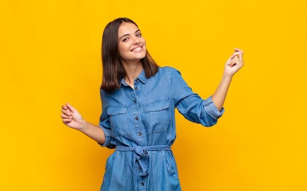 Giovane bella donna sorridente, spensierata, rilassata e felice, ballare e ascoltare musica, divertirsi a una festa