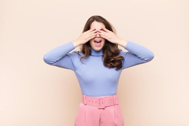 Giovane donna graziosa che sorride e si sente felice, coprendosi gli occhi con entrambe le mani e aspettando un'incredibile sorpresa contro il muro beige