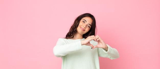 Giovane bella donna che sorride e si sente felice, carina, romantica e innamorata, a forma di cuore con entrambe le mani