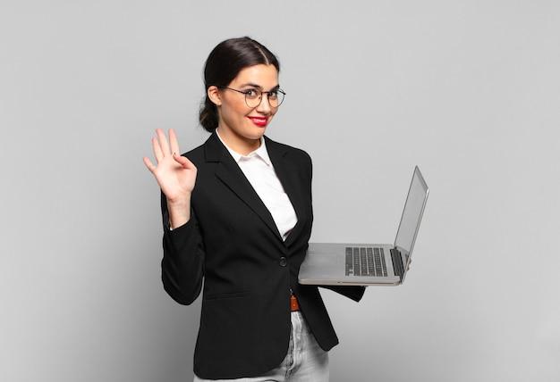 Giovane bella donna che sorride allegramente e allegramente, agitando la mano, accogliendoti e salutandoti o salutandoti. concetto di laptop