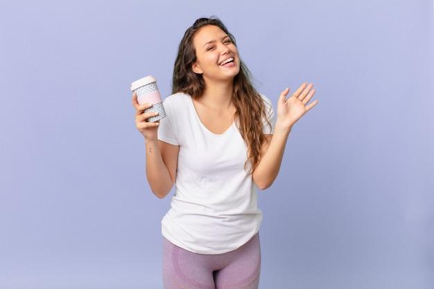 Giovane bella donna che sorride felice, agitando la mano, accogliendoti e salutandoti e tenendo in mano un caffè