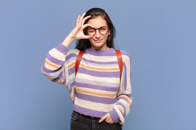 Giovane donna graziosa che sorride felicemente con la faccia buffa, scherzando e guardando attraverso lo spioncino, spiando i segreti. concetto di studente