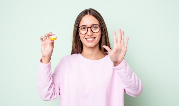 Giovane donna graziosa che sorride e che sembra amichevole, mostrando il numero cinque. concetto di lenti a contatto