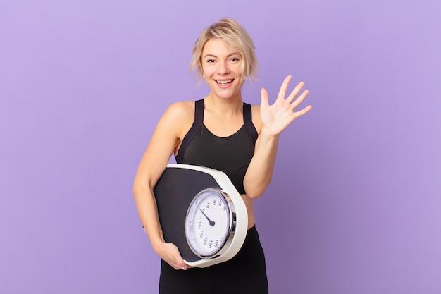Giovane donna graziosa che sorride e che sembra amichevole, mostrando il numero cinque. concetto di dieta