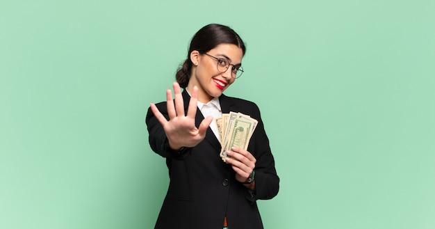 Giovane bella donna sorridente e dall'aspetto amichevole, mostrando il numero cinque o il quinto con la mano in avanti, conto alla rovescia. concetto di affari e banconote