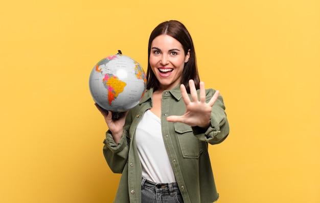 Giovane donna graziosa che sorride e sembra amichevole, mostrando il numero cinque o quinto con la mano in avanti, conto alla rovescia