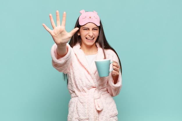 Giovane bella donna che sorride e sembra amichevole, mostrando il numero cinque o il quinto con la mano in avanti, conto alla rovescia