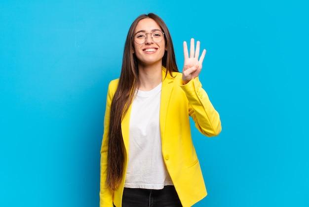 Giovane donna graziosa che sorride e sembra amichevole, mostrando il numero quattro o quarto con la mano in avanti, contando alla rovescia
