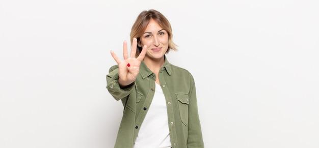 Giovane donna graziosa che sorride e sembra amichevole, mostrando il numero quattro o il quarto con la mano in avanti, contando alla rovescia