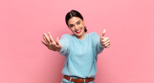 Giovane bella donna sorridente e dall'aspetto amichevole, mostrando il numero sei o il sesto con la mano in avanti, conto alla rovescia