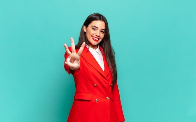Giovane bella donna sorridente e dall'aspetto amichevole, mostrando il numero tre o il terzo con la mano in avanti, conto alla rovescia. concetto di business