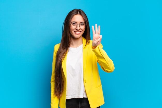 Giovane donna graziosa che sorride e sembra amichevole, mostrando il numero tre o terzo con la mano in avanti, contando alla rovescia