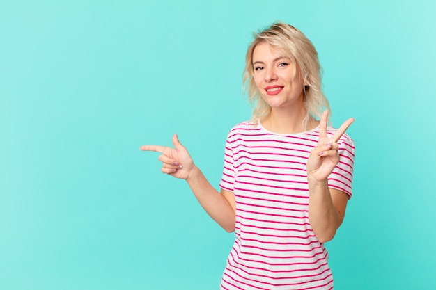 Giovane donna graziosa che sorride e che sembra amichevole, mostrando il numero due. copia il concetto di spazio