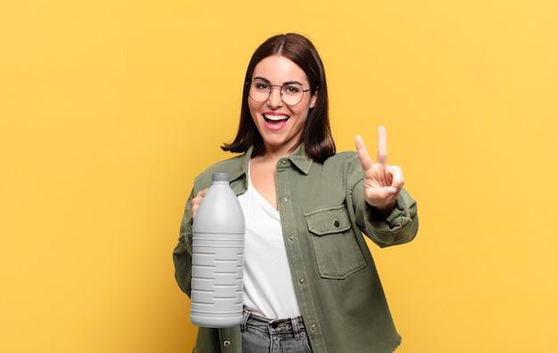 Giovane donna graziosa che sorride e sembra amichevole, mostrando il numero due o il secondo con la mano in avanti, conto alla rovescia