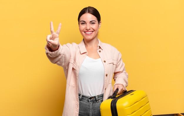 Giovane donna graziosa che sorride e sembra felice, spensierata e positiva, gesticolando vittoria o pace con una mano