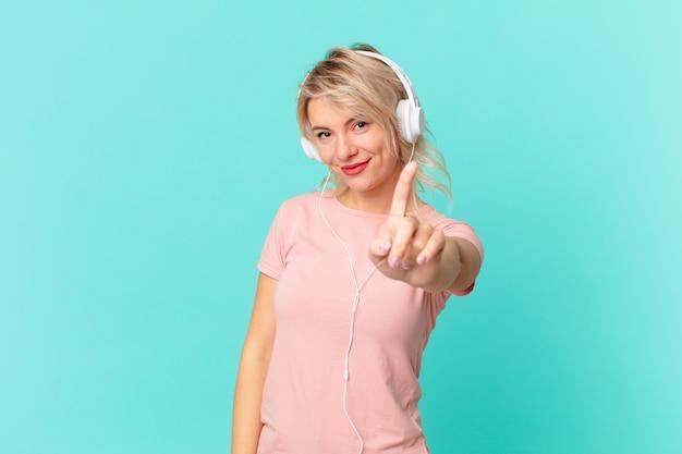 Giovane donna graziosa che sorride con orgoglio e sicurezza facendo il numero uno. ascoltando il concetto di musica