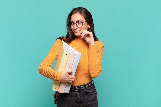 Giovane donna graziosa che sorride con un'espressione felice e sicura con la mano sul mento, chiedendosi e guardando di lato. concetto di studente