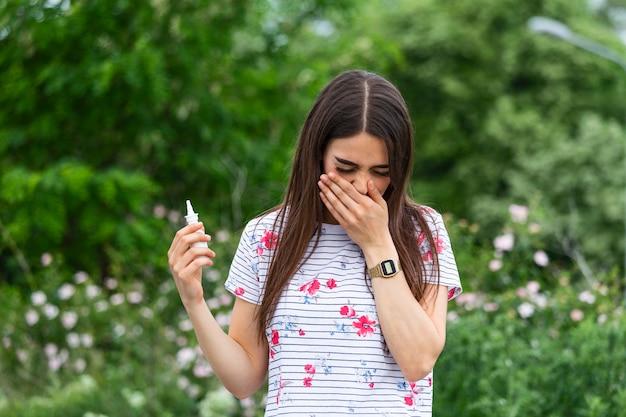 Giovane donna graziosa che starnutisce davanti all'albero in fiore.