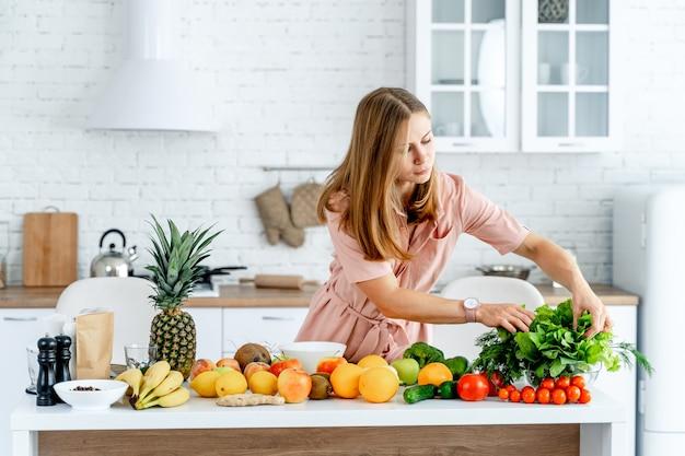 Giovane e bella donna in piedi presso la cucina piena di frutta e verdura negli interni moderni