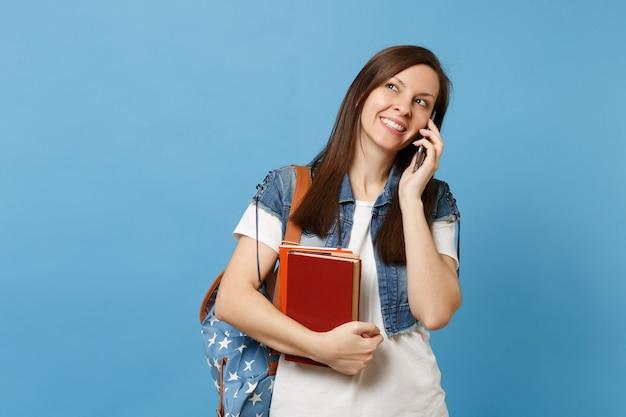 Giovane studentessa graziosa con lo zaino che tiene i libri di scuola che parla sul telefono cellulare che conduce una conversazione piacevole isolata su fondo blu. istruzione nel concetto di college universitario di liceo.