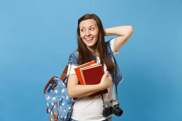 Giovane studentessa graziosa con la macchina fotografica d'epoca retrò sul collo che guarda da parte tenendo la mano sulla testa e tenendo i libri di scuola isolati su sfondo blu. istruzione al college universitario di scuola superiore.