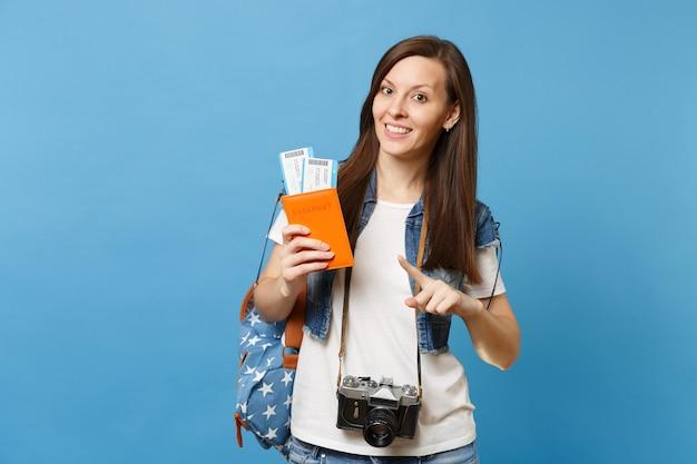 Giovane studentessa graziosa con la macchina fotografica d'epoca retrò sul collo che punta il dito indice sul passaporto, biglietti per la carta d'imbarco isolati su sfondo blu. istruzione in università all'estero. volo aereo.