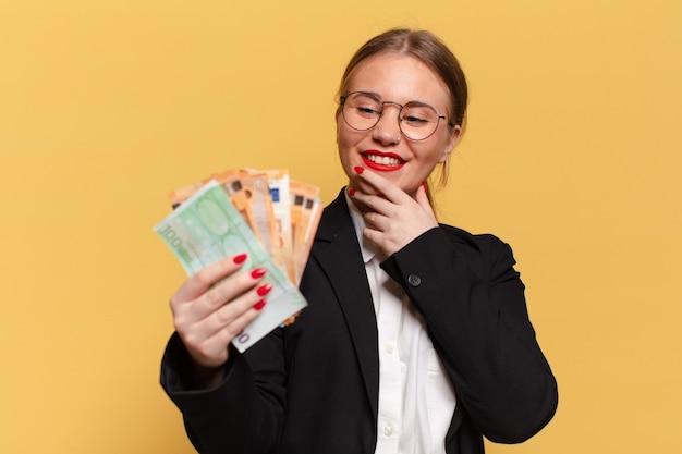 Giovane donna graziosa. pensare o dubitare dell'espressione delle banconote in euro concept