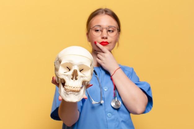 Giovane donna graziosa. pensare o dubitare del concetto di infermiera di espressione