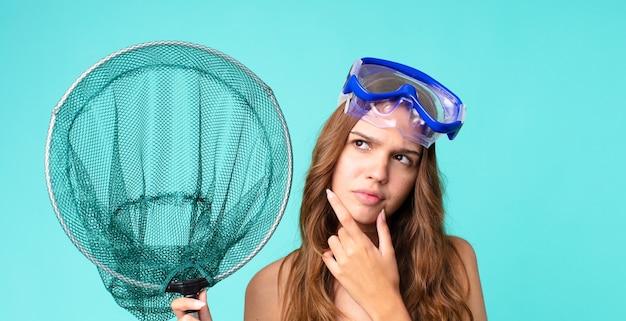 Giovane bella donna che pensa, si sente dubbiosa e confusa con gli occhiali e una rete da pesca