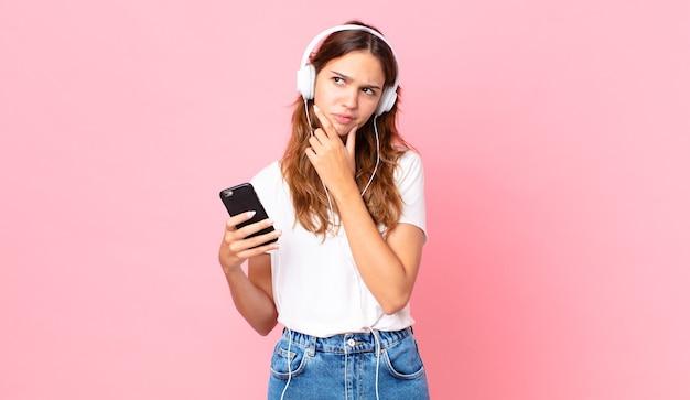 Giovane bella donna che pensa, si sente dubbiosa e confusa con le cuffie e uno smartphone