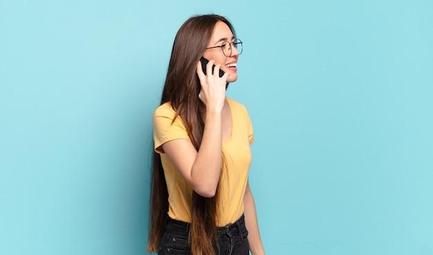 Giovane donna graziosa che utilizza il suo cellulare.