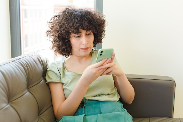 Giovane donna graziosa che utilizza il suo telefono intelligente nella nuova casa